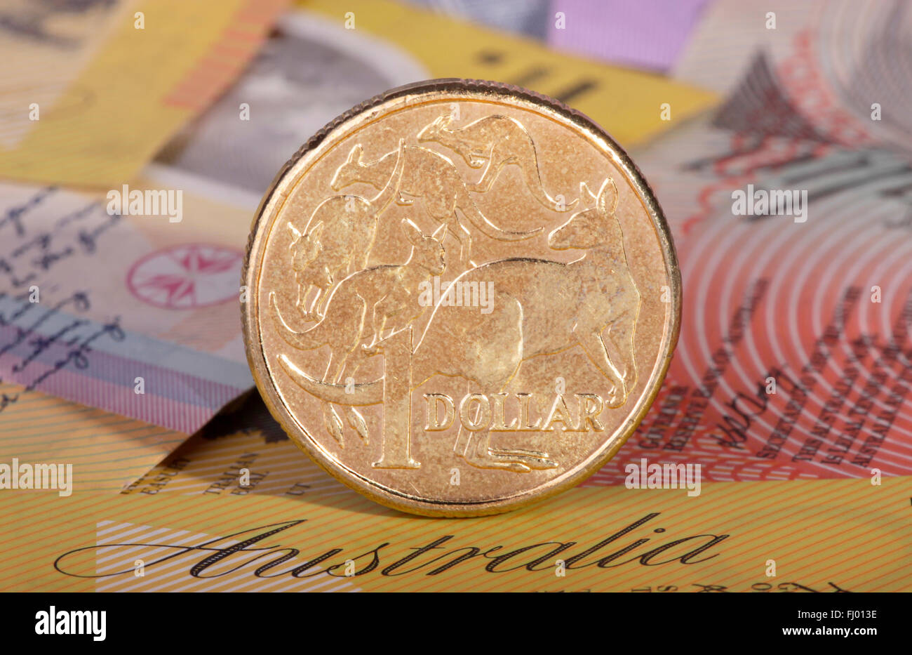 One Australian dollar coin with a background of Australian bank notes. - Stock Image