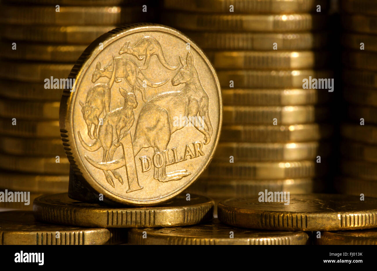 An Australian dollar coin with stacks of coins in background. - Stock Image
