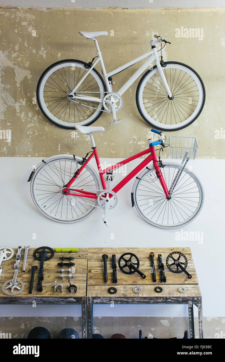 Two custom-made bicycles hanging on the wall in a store - Stock Image
