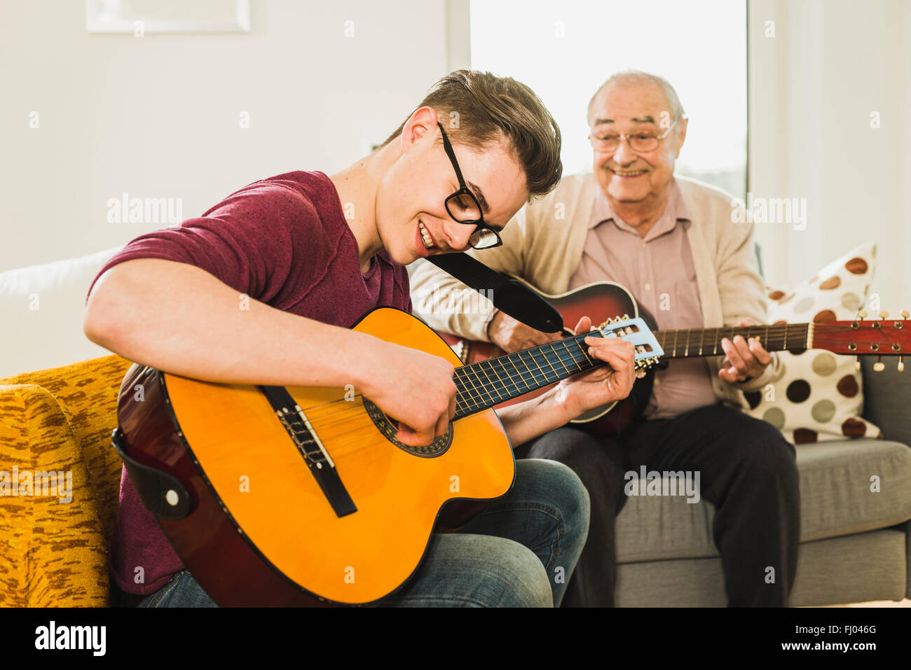 Grandfather and grandson playing guitar together - Stock Image