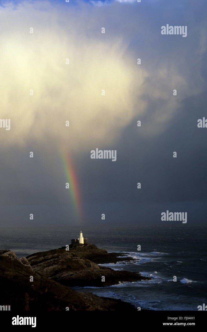 There's light at the end of the Rainbow. A rainbow falls from the clouds in a shaft of light at Mumbles Light house,Swansea Stock Photo