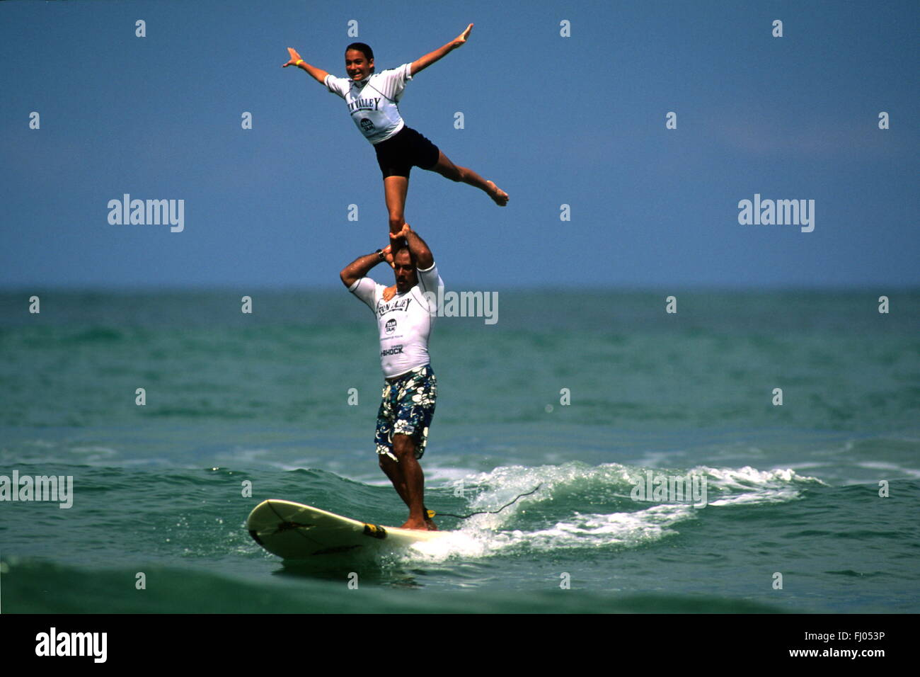 tandem surfing choreographed by the waves - Stock Image