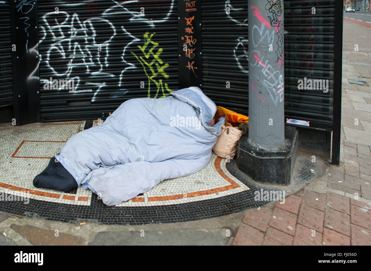 Homeless Person Sleeps Rough in Shop Door Way with Graffiti in Stokes Croft Bristol - Stock Image
