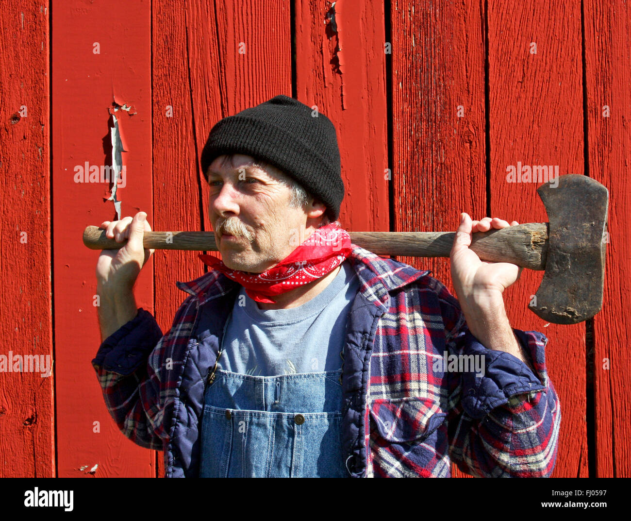 lumberjack portrait in front of a barn with an ax on his shoulders - Stock Image
