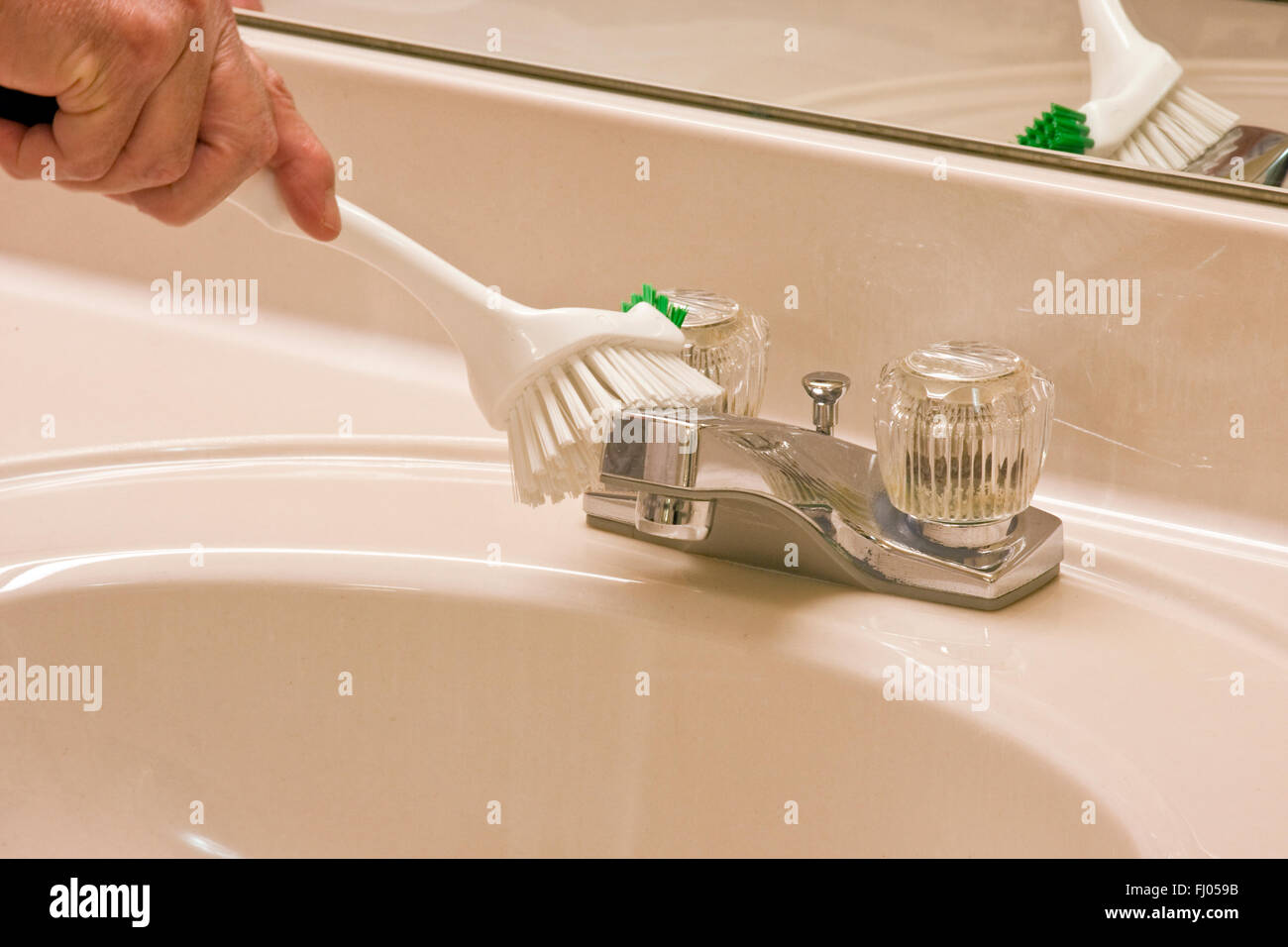 bathroom sink being cleaned with a scrub brush - Stock Image