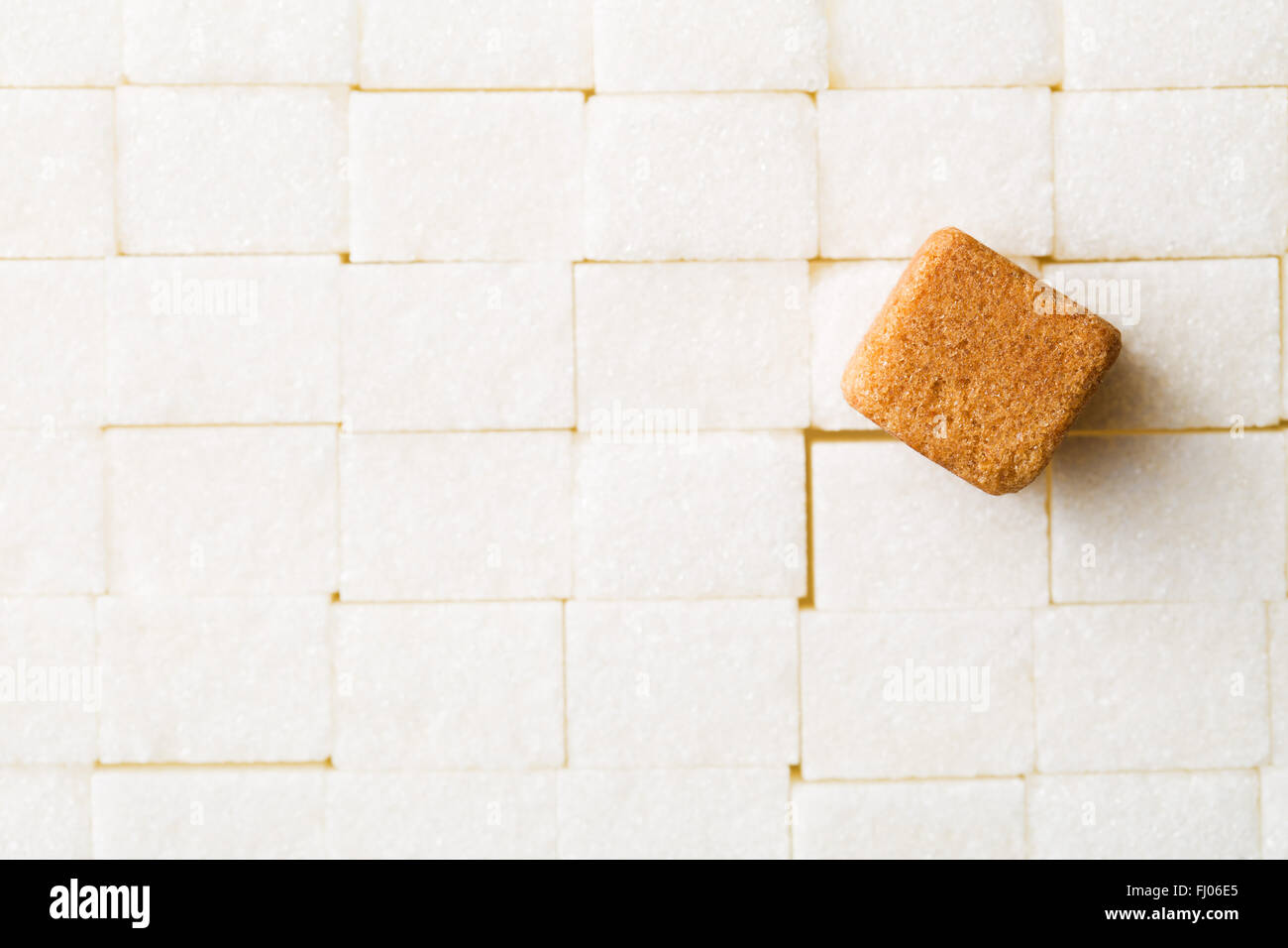 the brown cane sugar cube on white sugar cubes - Stock Image
