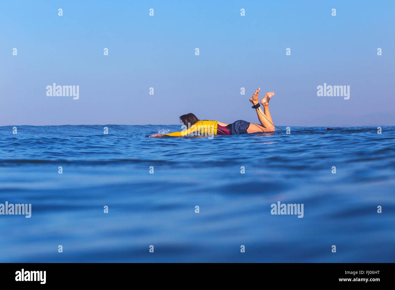 Indonesia, Bali, woman lying on her surfboard floating in the water - Stock Image