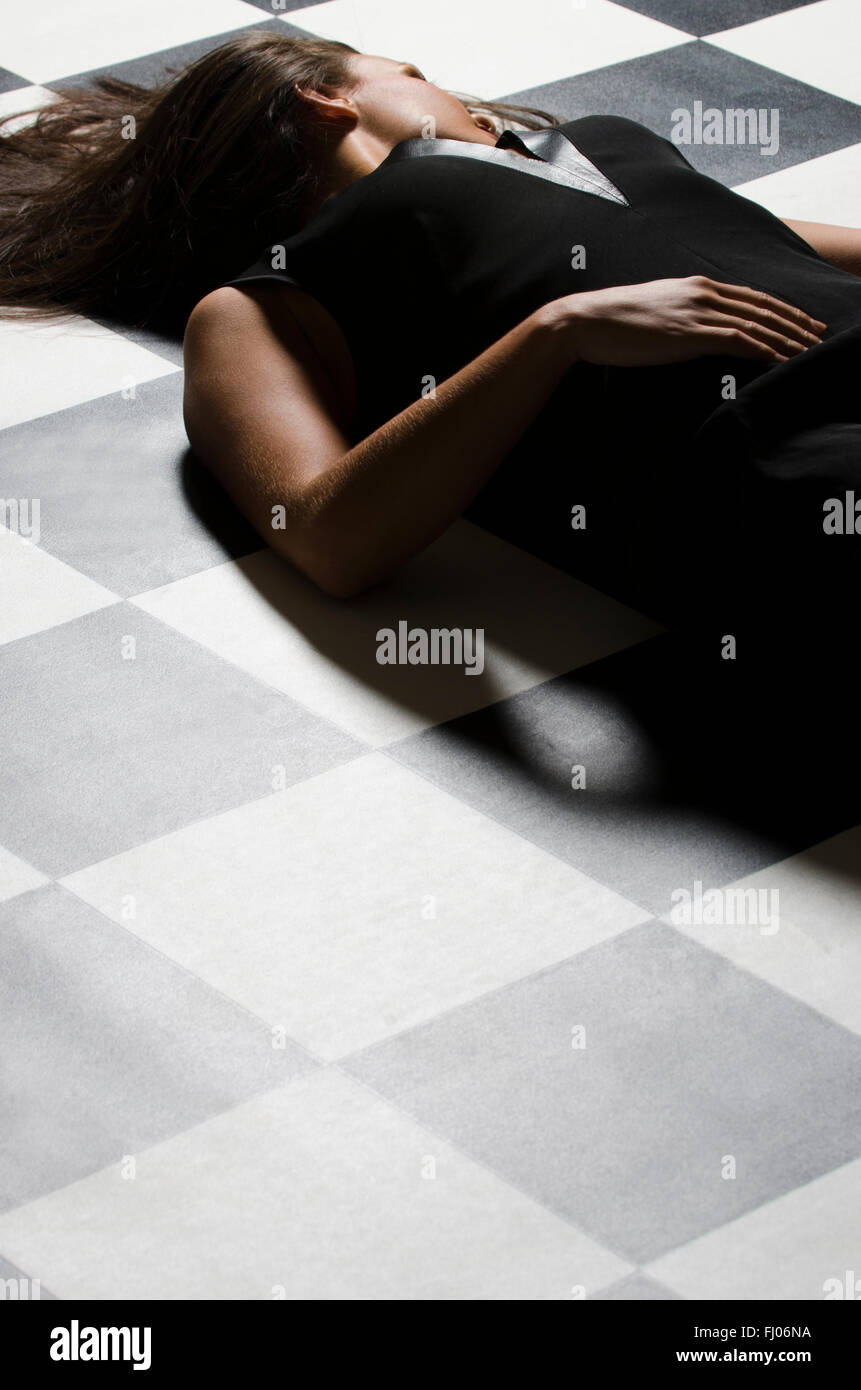 Dead woman body on checkered floor - Stock Image