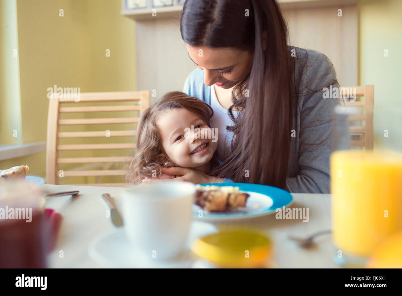 Portrait of smiling little girl and her mother at breakfast table - Stock Image