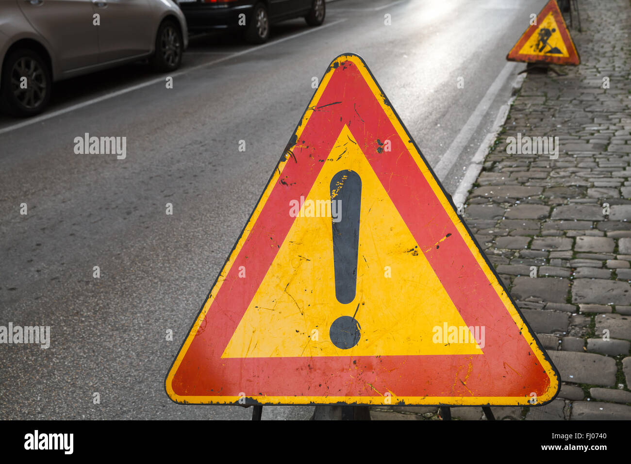 Bright red and yellow triangle warning road sign with exclamation mark on the roadside - Stock Image