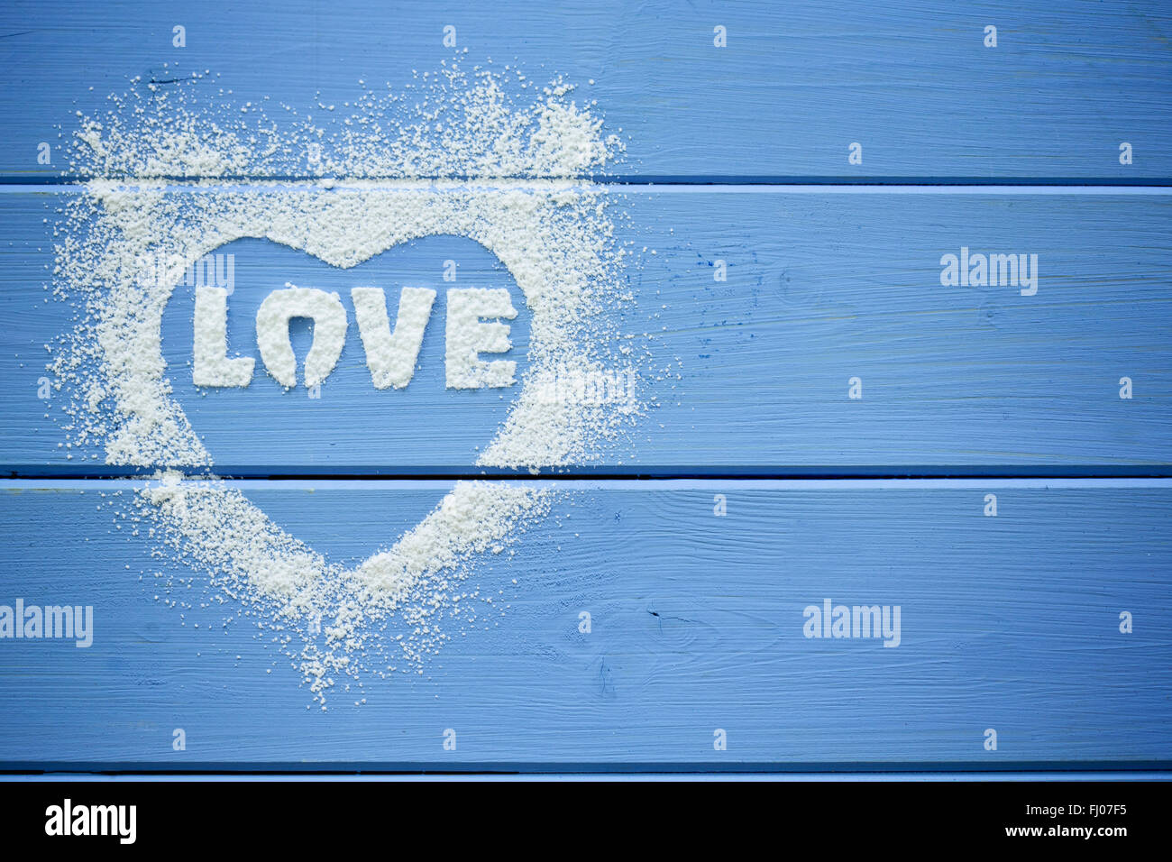 Heart shape and the word 'Love' stenciled with icing sugar - Stock Image
