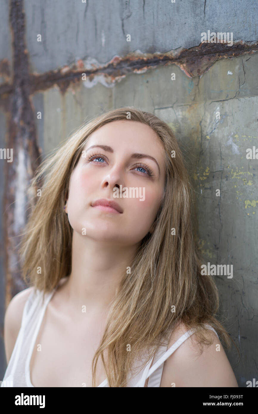 Young woman leaning against a rusty wall - Stock Image