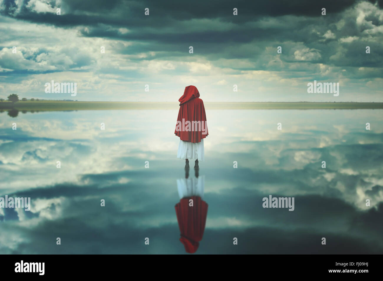 Red hooded woman in a strange landscape with clouds. Fantasy and surreal - Stock Image