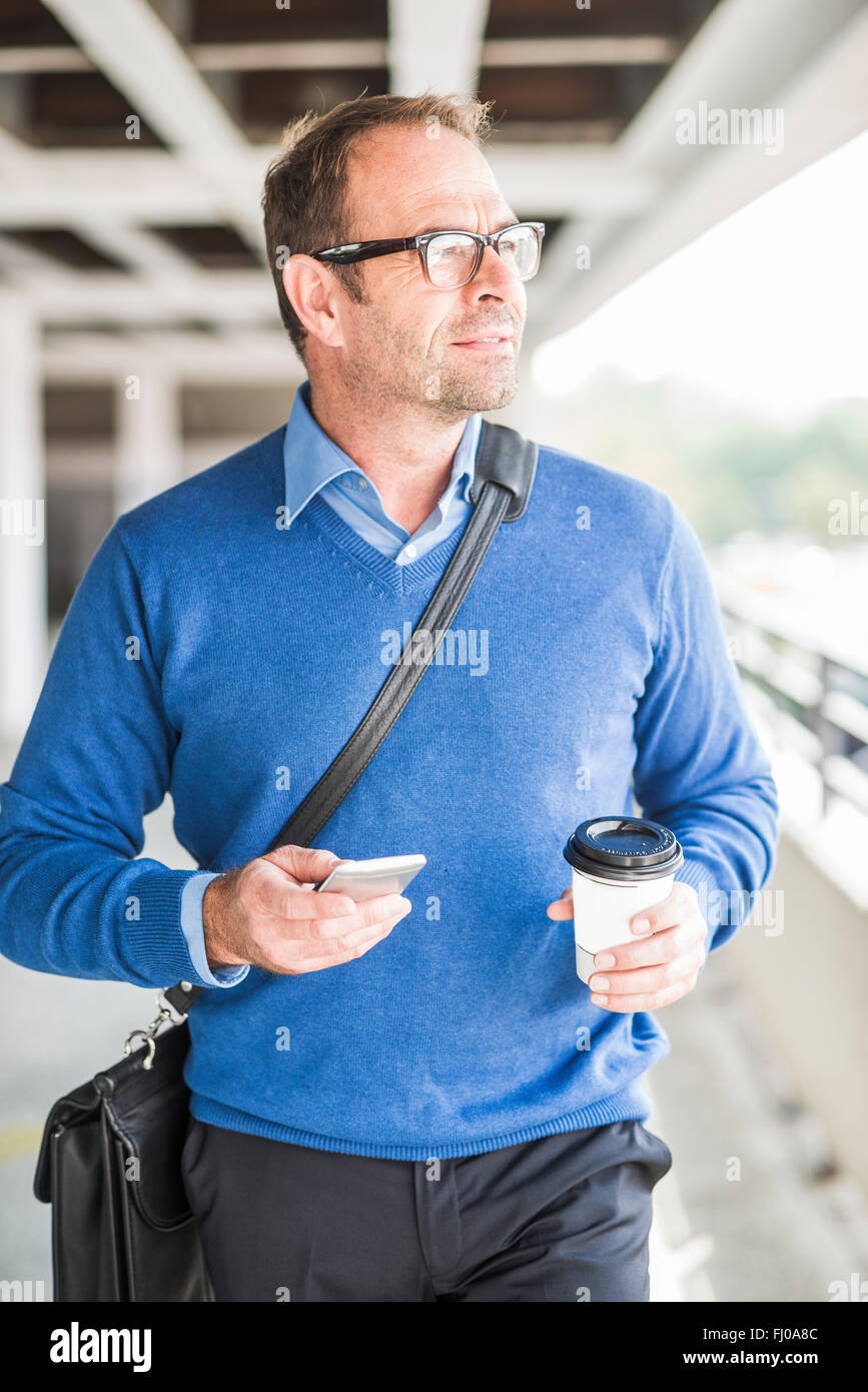 Businessman with cell phone and coffee to go on the move - Stock Image