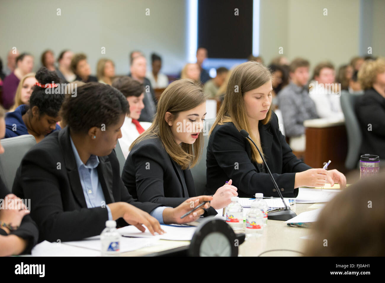 Teens posing as defense attorneys in mock trial for high school students participate in proceedings in county courtroom - Stock Image