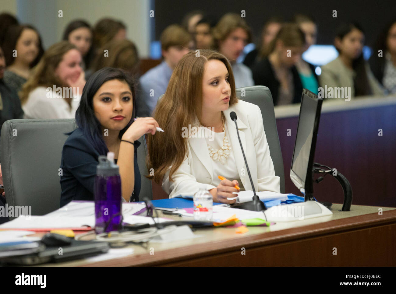 Teen girl posing as defense attorney speaks during mock trial for high school students in Texas courtroom - Stock Image