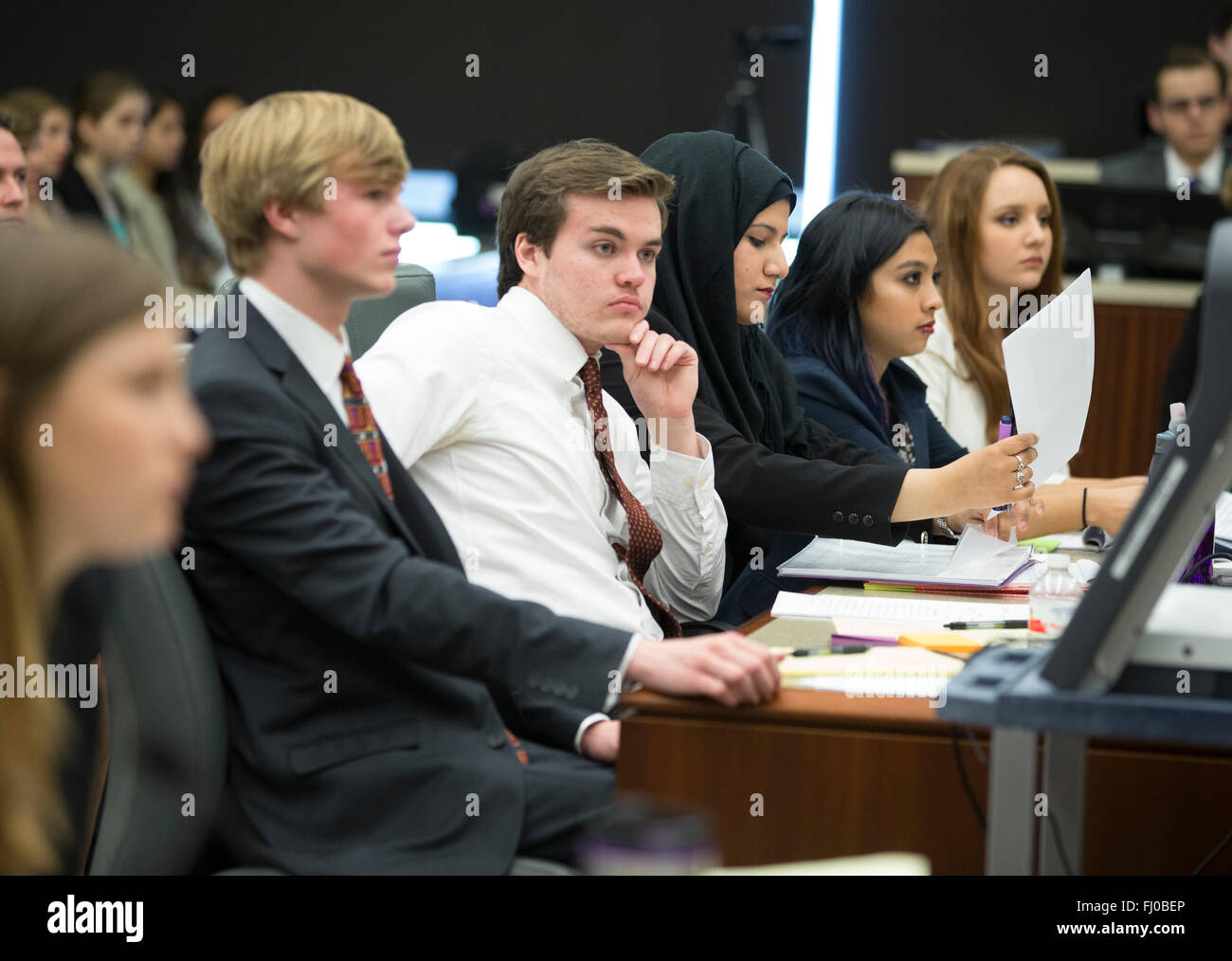 Teens posing as prosecuting attorneys in mock trial for high school students listen to proceedings in county courtroom - Stock Image