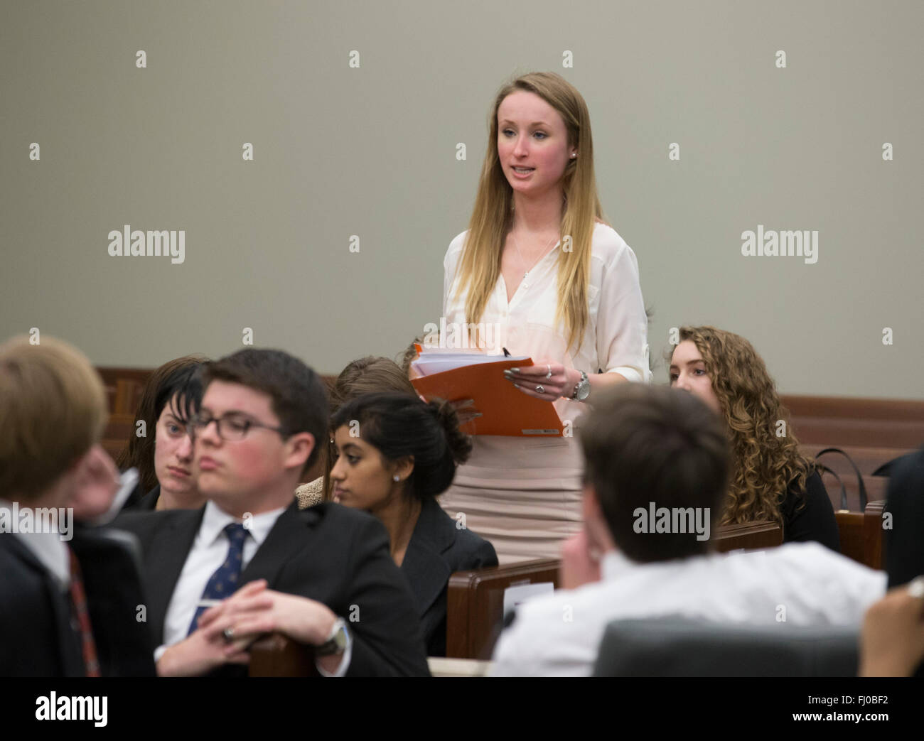 Teen girl acting as jury foreman announces her panel's verdict during high school mock trial re-enacting dating - Stock Image