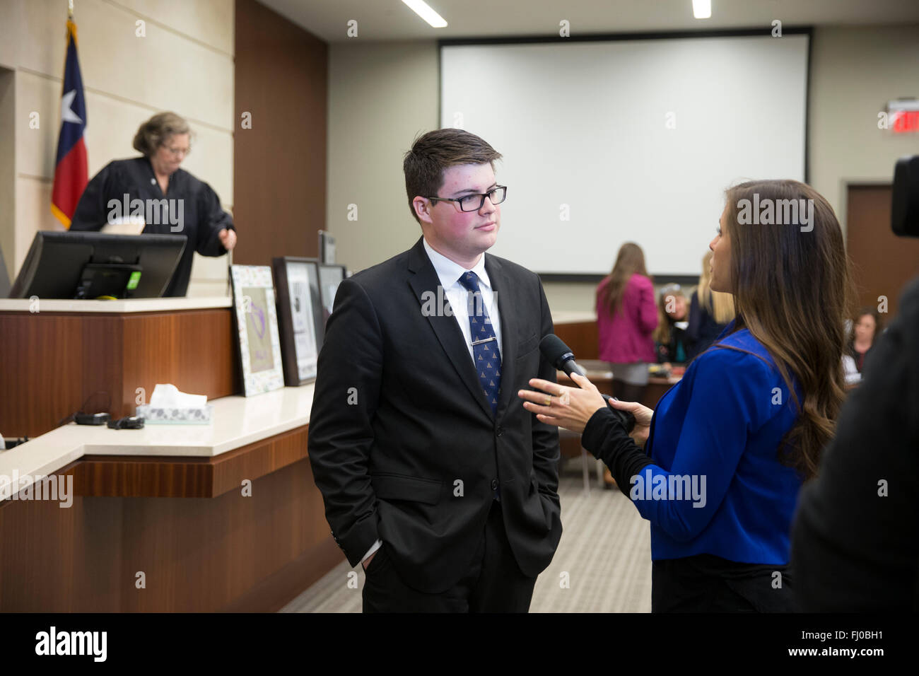 High school students serving as attorneys in mock trial designed to raise awareness of dating abuse talk in courtroom - Stock Image