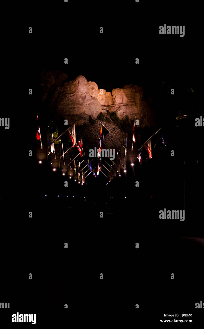 Mount Rushmore memorial illuminated during night. President's path, which is adorned with flags. - Stock Image