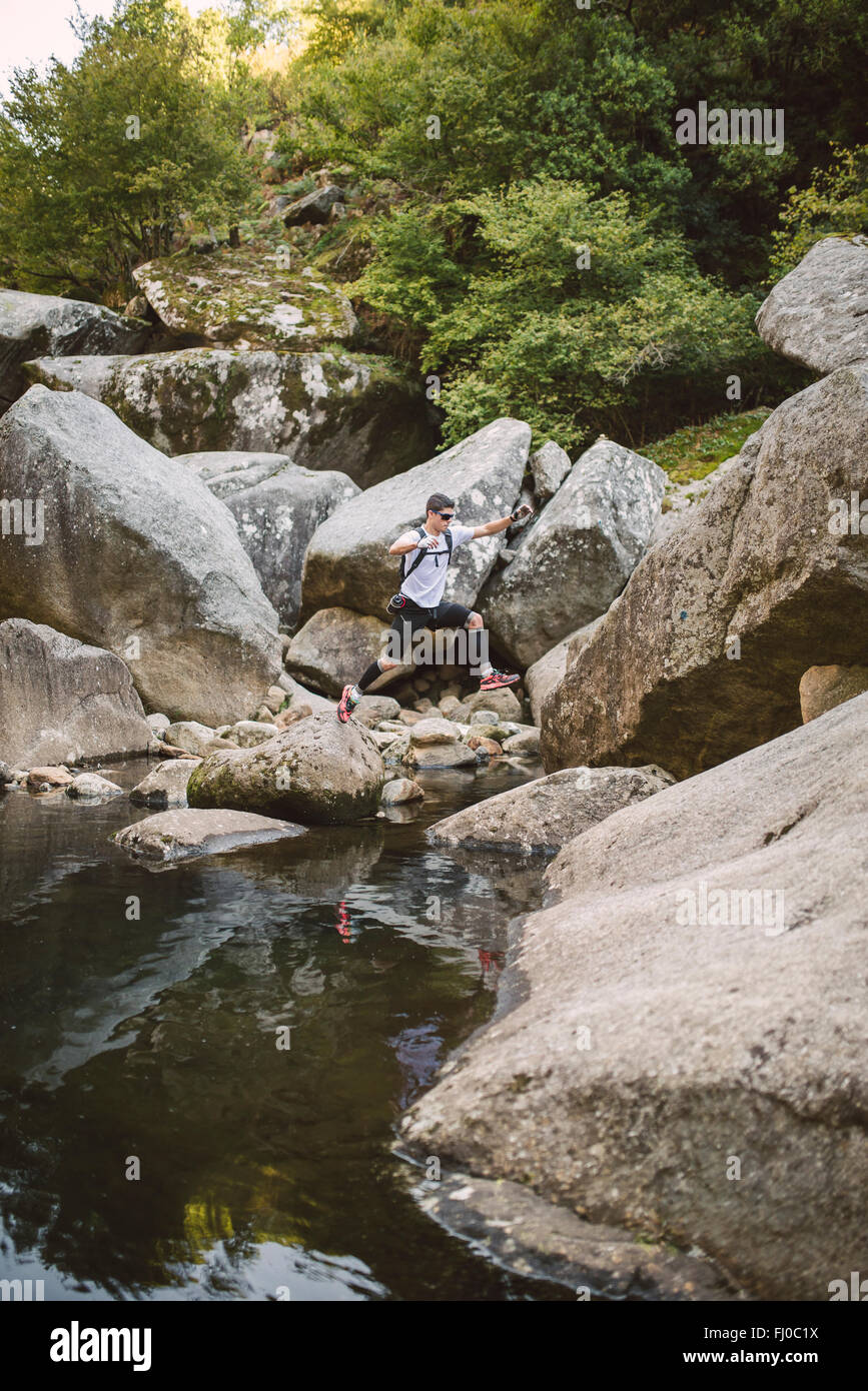 Spain, A Capela, ultra trail runner crossing a river - Stock Image