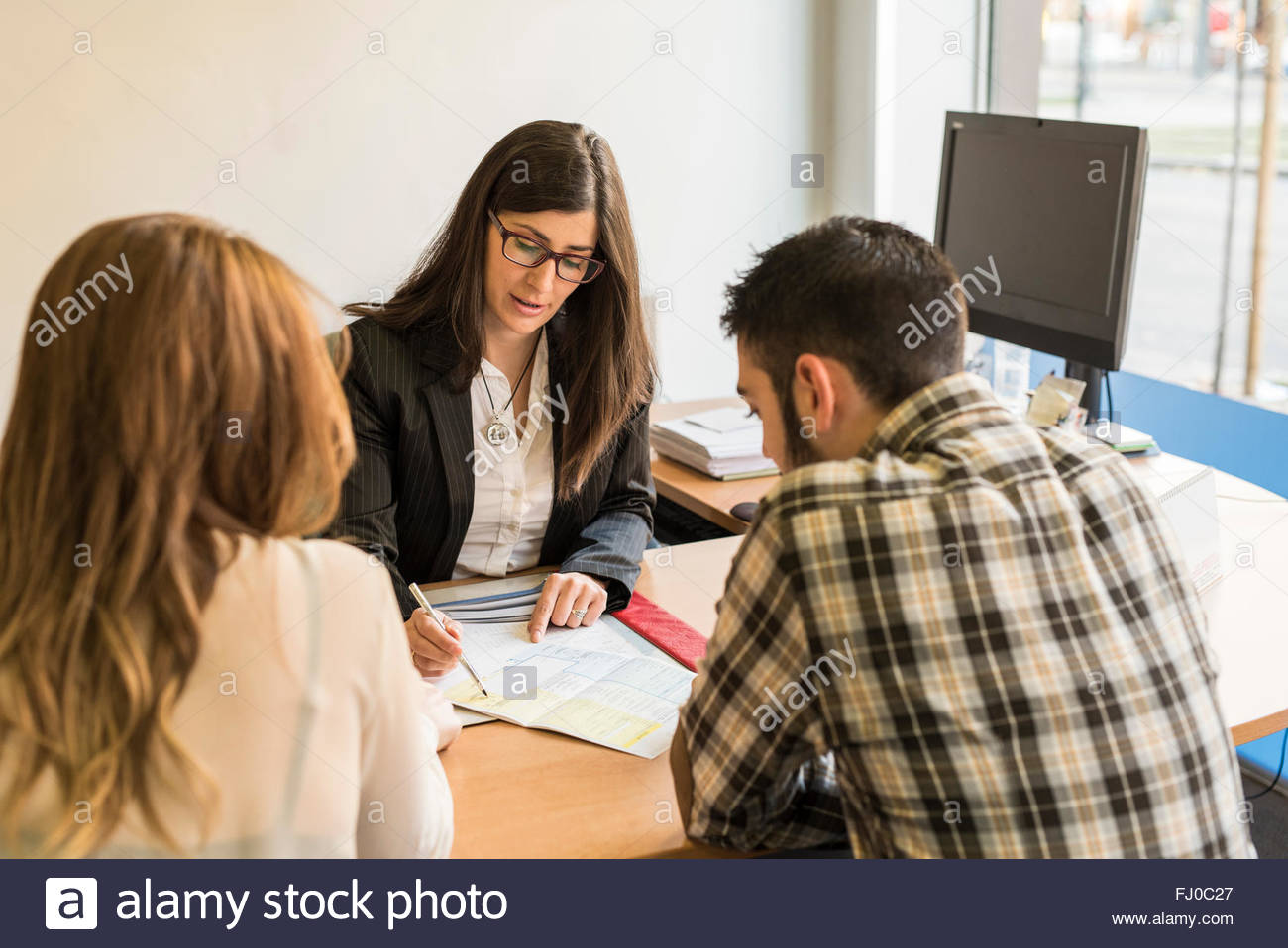 Clerk helping young couple filling in document - Stock Image