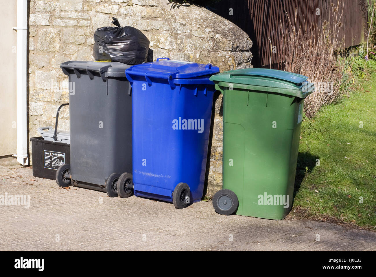 Rubbish bins standing on a driveway. - Stock Image