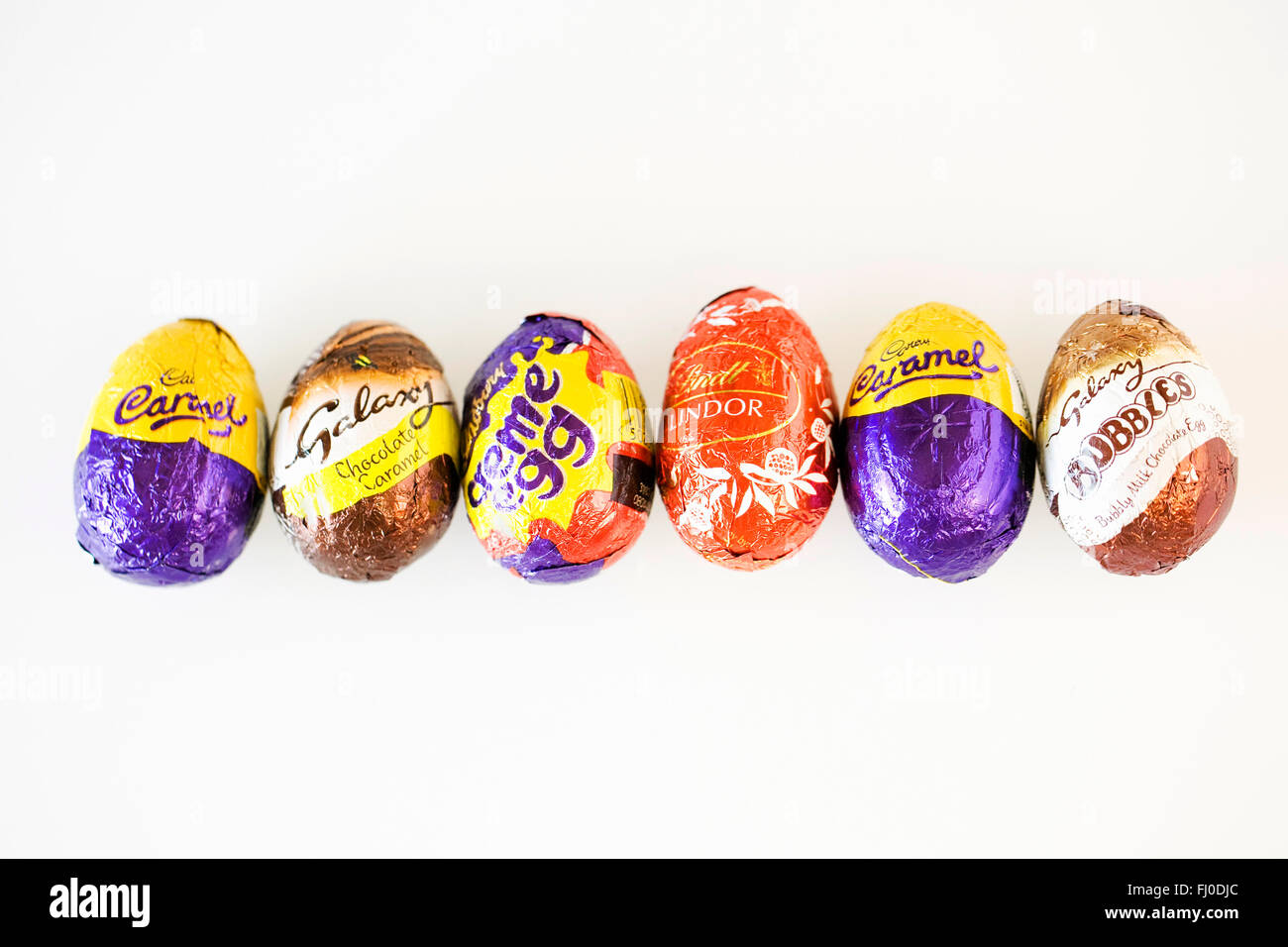 Assorted chocolate eggs on a white background. - Stock Image