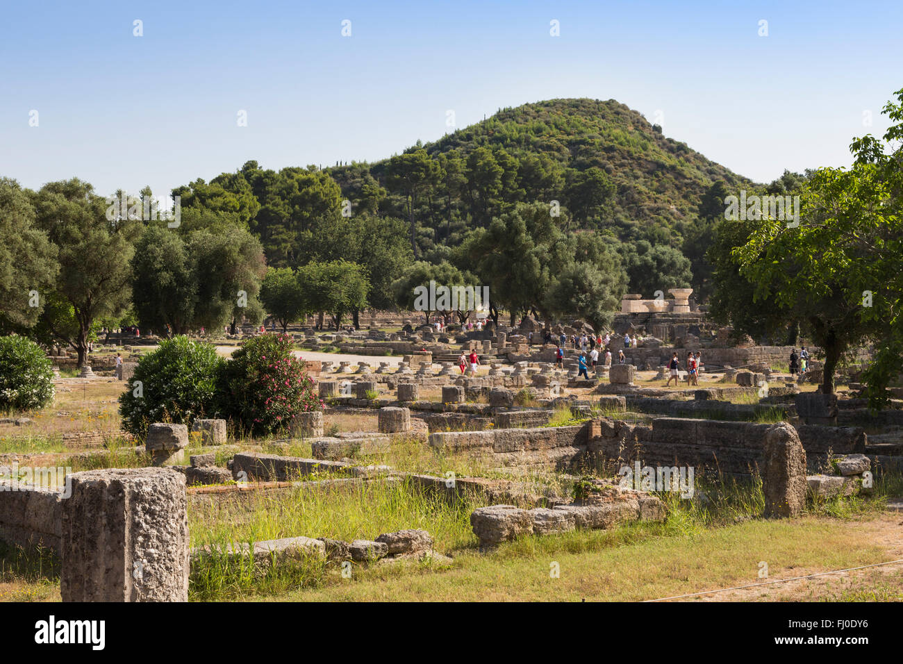 Olympia, Peloponnese, Greece.  Ancient Olympia.  Groups of visitors strolling through the ruins. - Stock Image