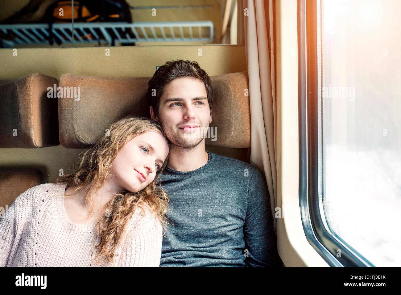 Smiling young couple in train car looking out of window - Stock Image