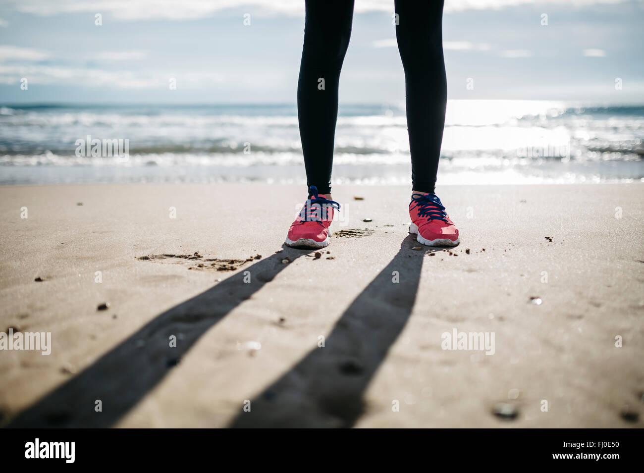 Legs and sneakers on the sand of a beach - Stock Image