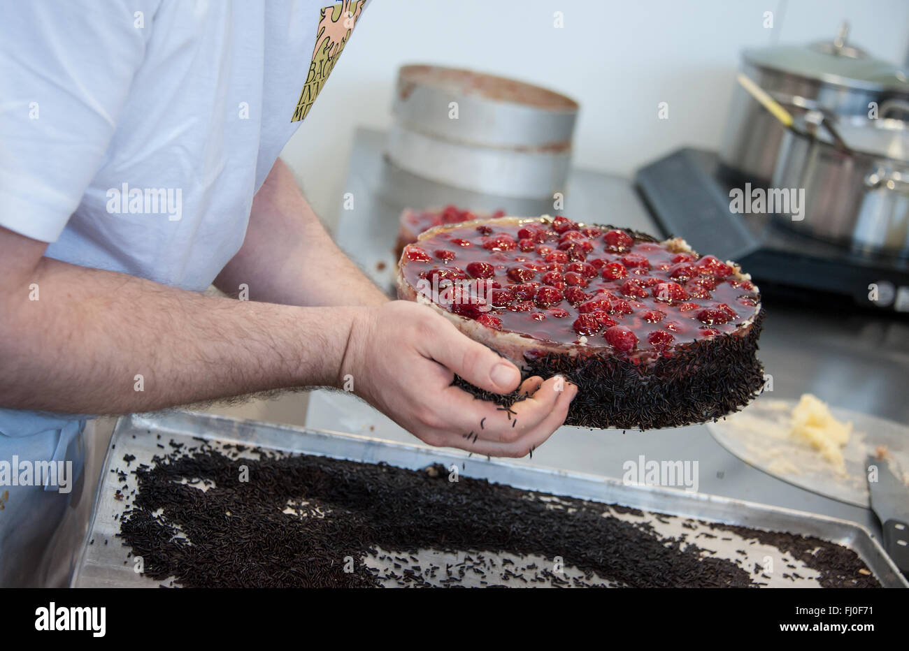 Munich, Germany. 26th Feb, 2016. A baker adds chocolate sprinkles to a raspberry cake at a booth at the Internationale Stock Photo