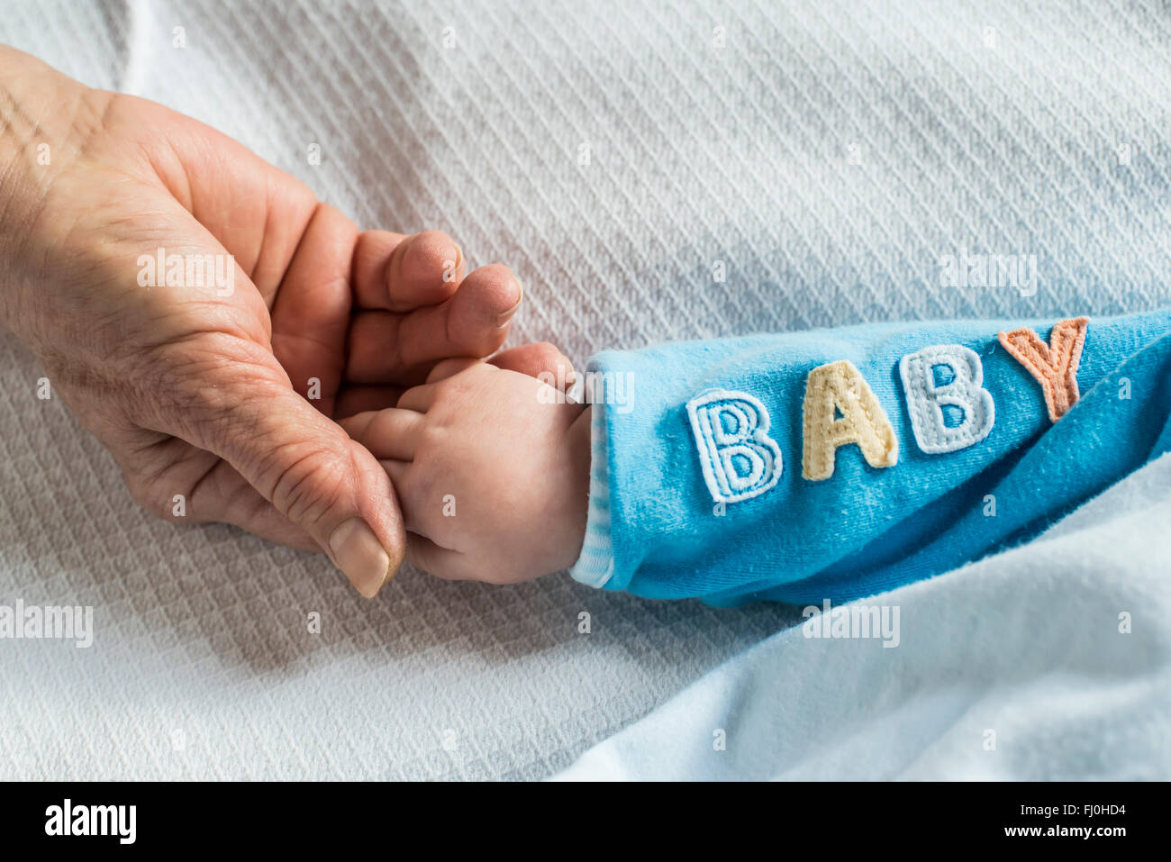 Senior woman's hand holding baby's hand - Stock Image