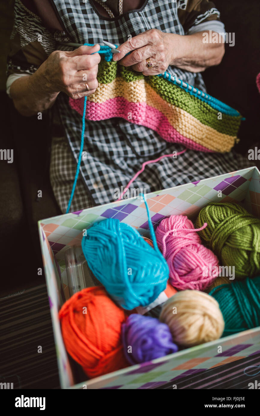 Box of different balls of wool and knitting senior woman - Stock Image
