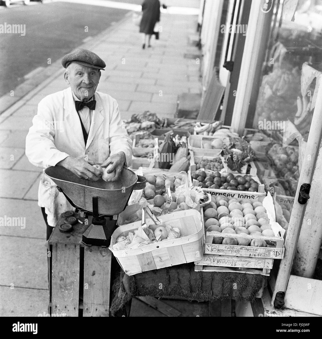 Fruit and vegetable shop man selling produce at independent high street shop in 1960s - Stock Image