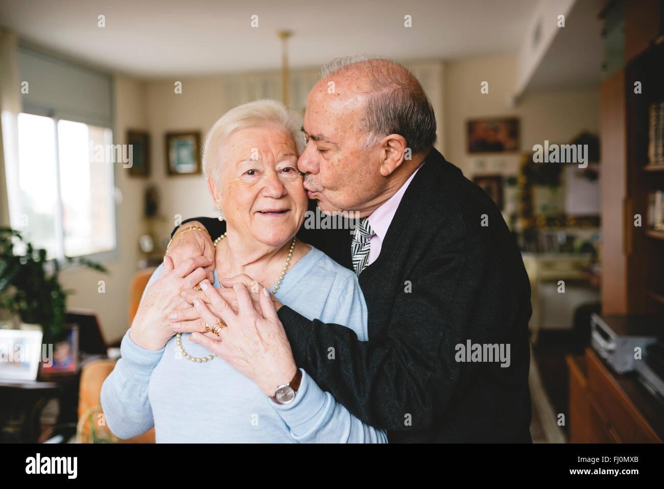 Senior couple hugging and kissing at home Stock Photo