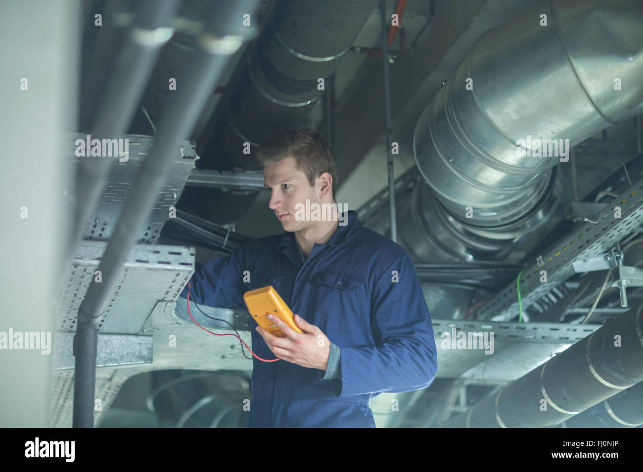 Young man in technical room checking pipe - Stock Image
