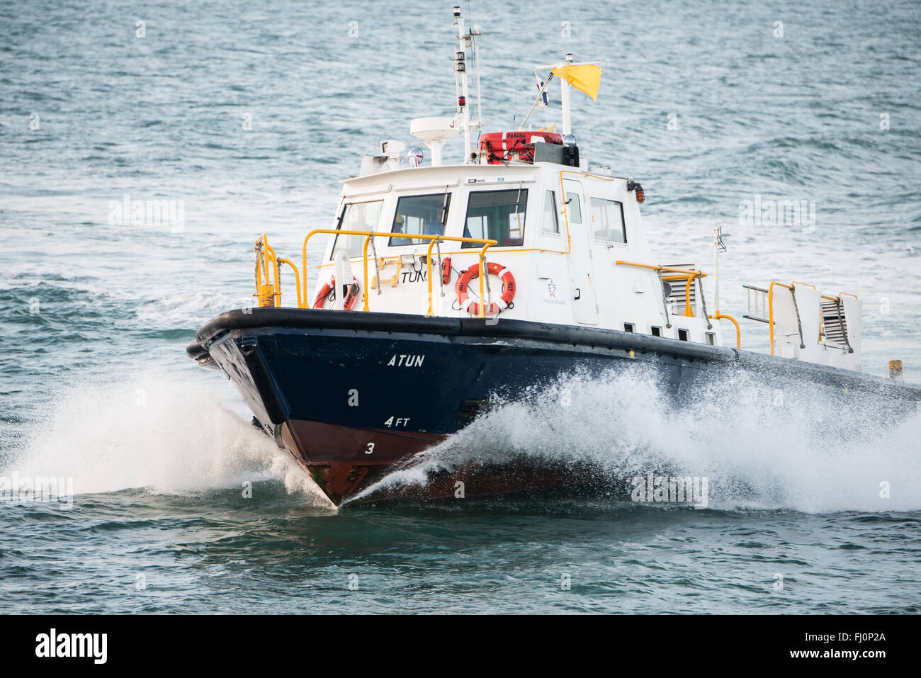 PANAMA CANAL, Panama--A pilot boat drops off a pilot to a ship about to enter the Panama Canal. Every ship entering - Stock Image