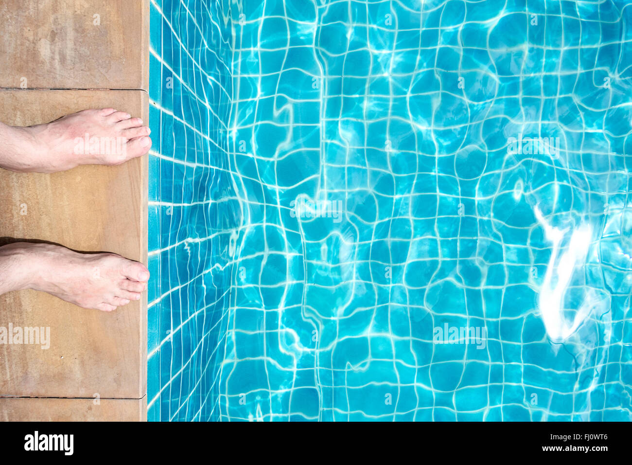 Feet of a man at pool edge - Stock Image