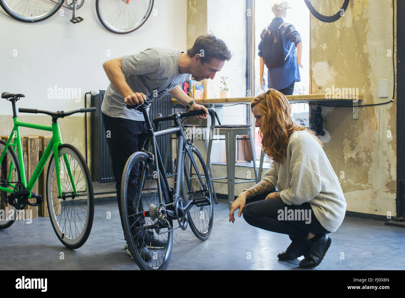 Salesman advising client in a custom-made bicycle store - Stock Image