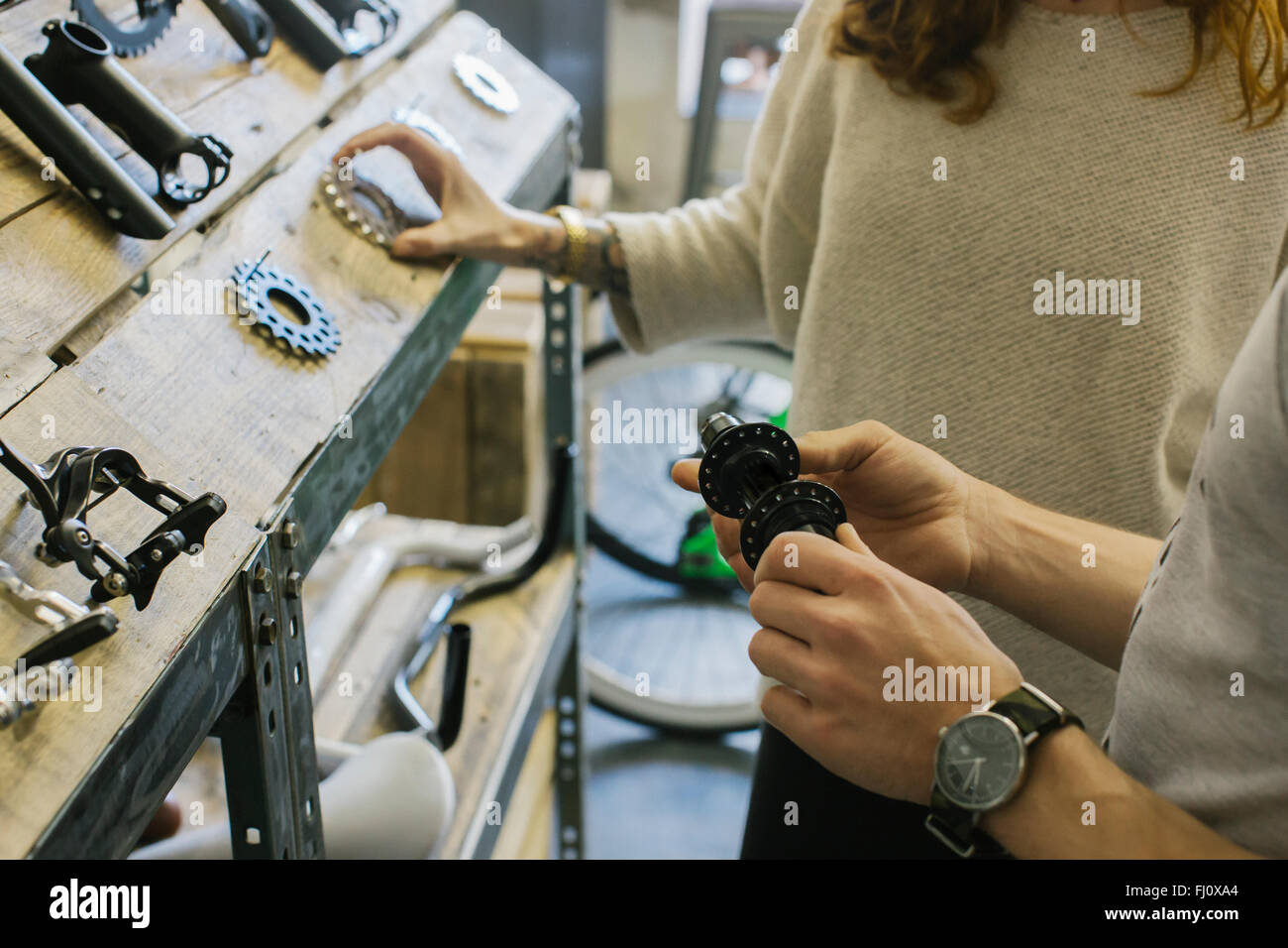 Man showing bicycle components to woman in a store - Stock Image