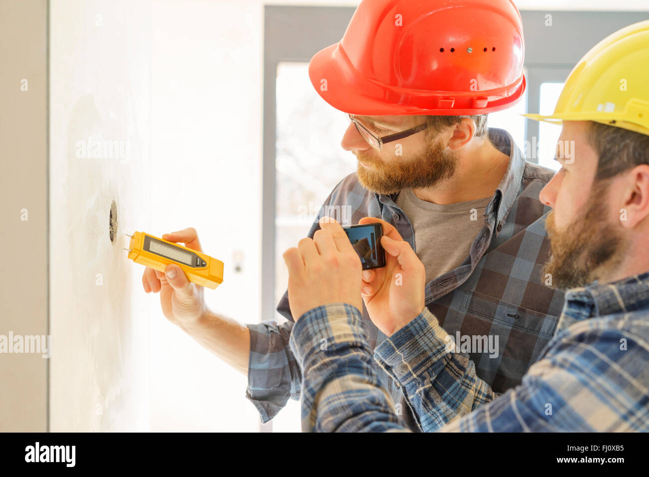 Two craftsmen with measuring device in construction site - Stock Image
