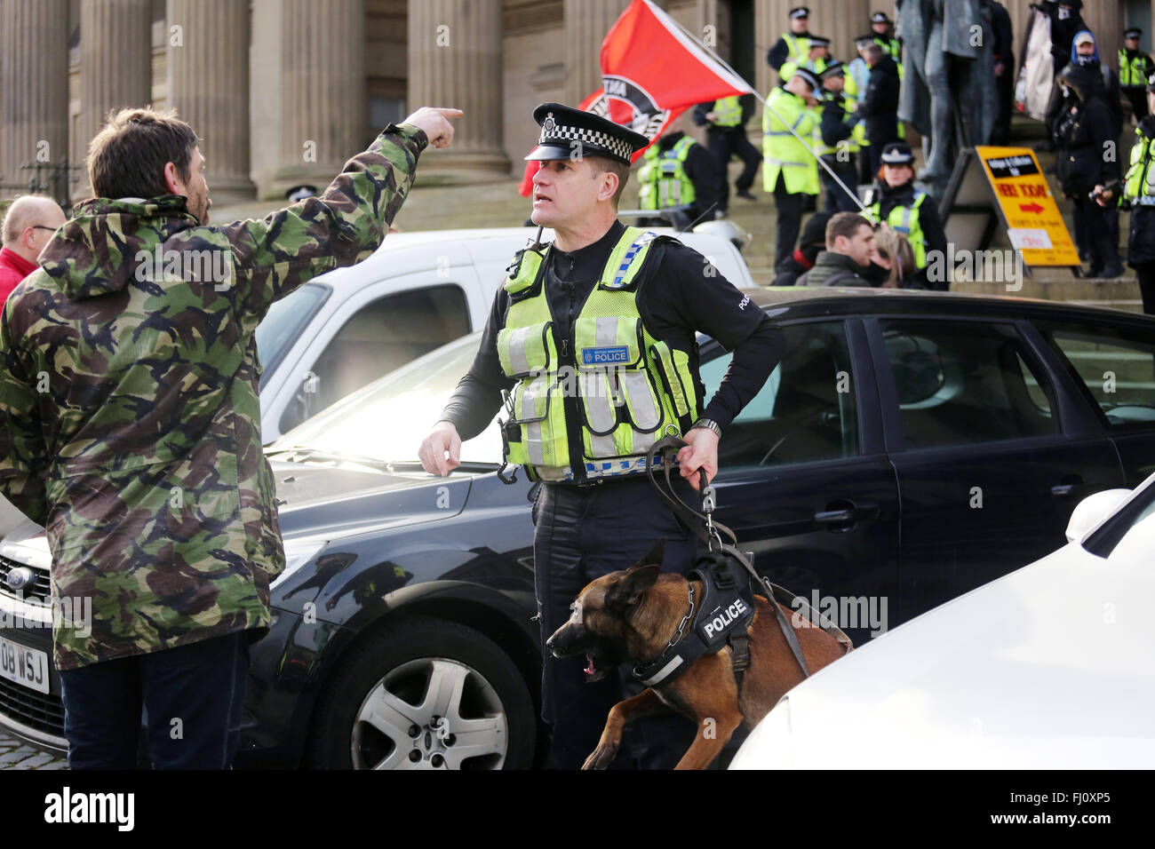 Liverpool, UK. 27th Feb, 2016. A Police Dog handler speaking to an anti racist protester in Liverpool, UK 27th February - Stock Image