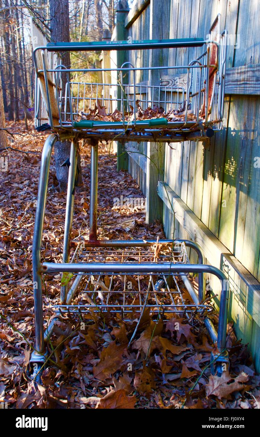Abandoned shopping cart against fence in woods - Stock Image