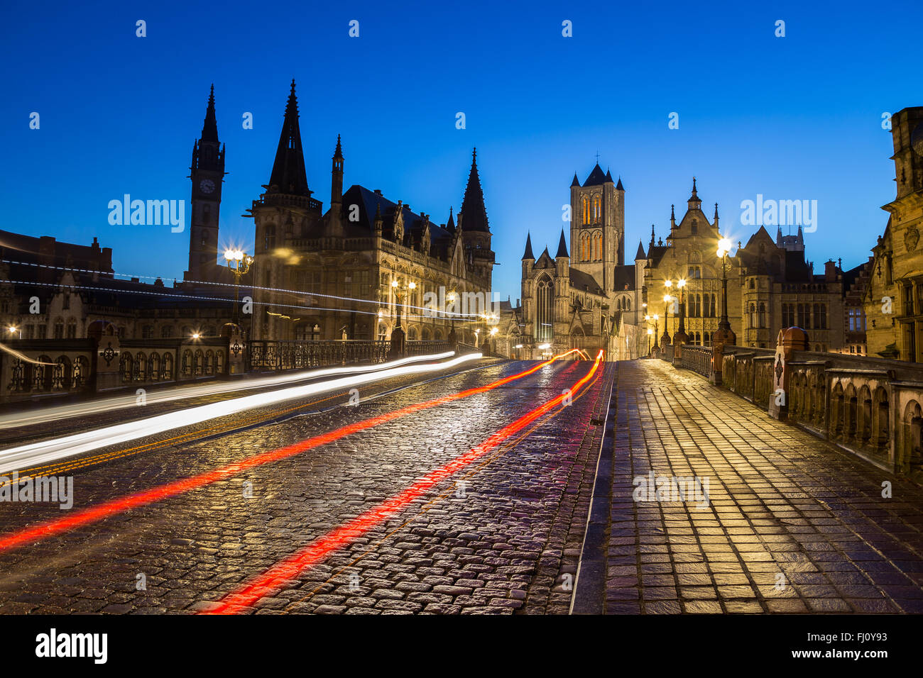 A view towards Saint Nicholas' Church in Ghent City Center at dusk in the morning. The trails of traffic can - Stock Image