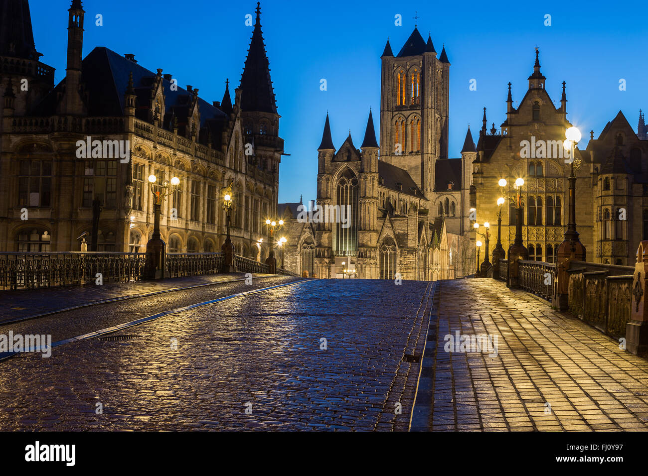 A view towards Saint Nicholas' Church in Ghent City Center at dusk in the morning. A cobbled road can be seen - Stock Image
