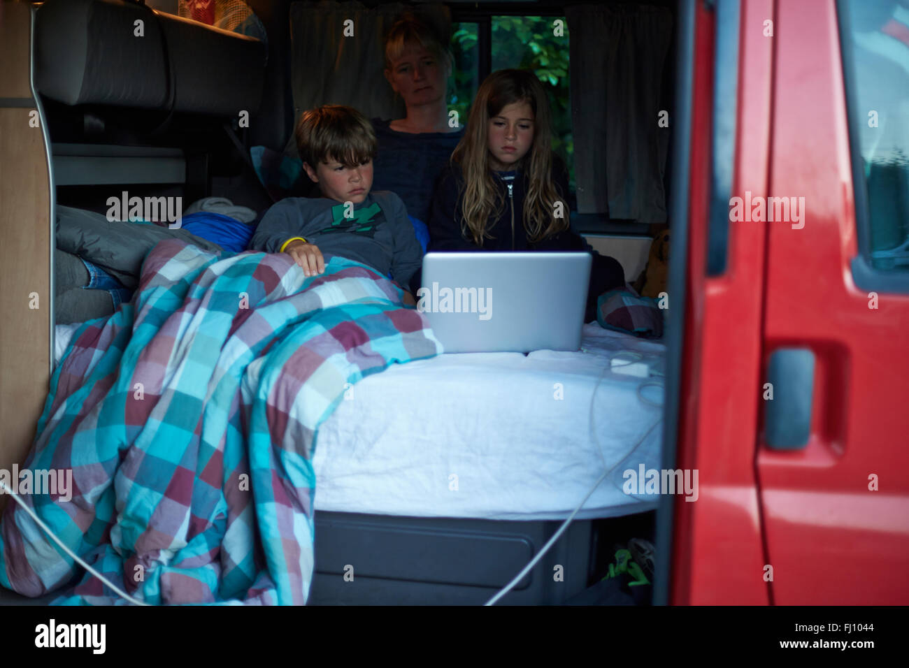 Mother and two children sitting on bed in a camper watching a movie with laptop Stock Photo