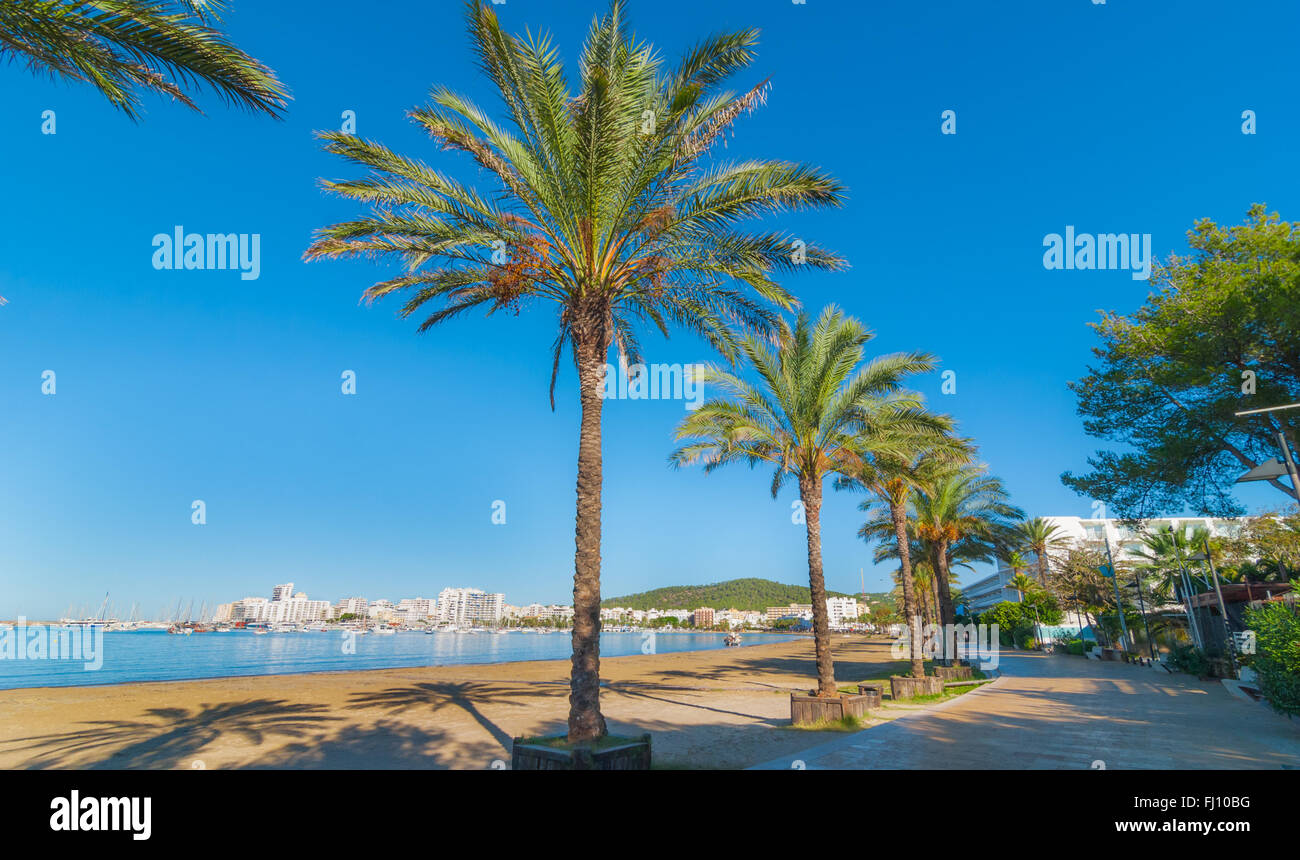 Mid morning sun on Ibiza waterfront.  Warm sunny day along the beach in St Antoni de Portmany Balearic Islands, Stock Photo