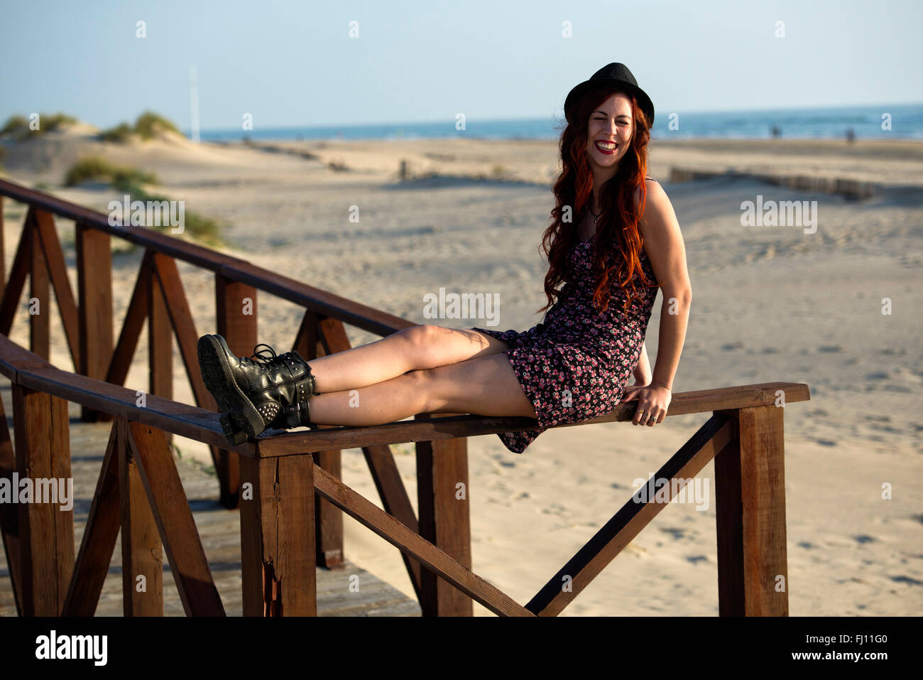 Spain, Cadiz, portrait of young redheaded woman sitting on railing of boardwalk at the beach Stock Photo