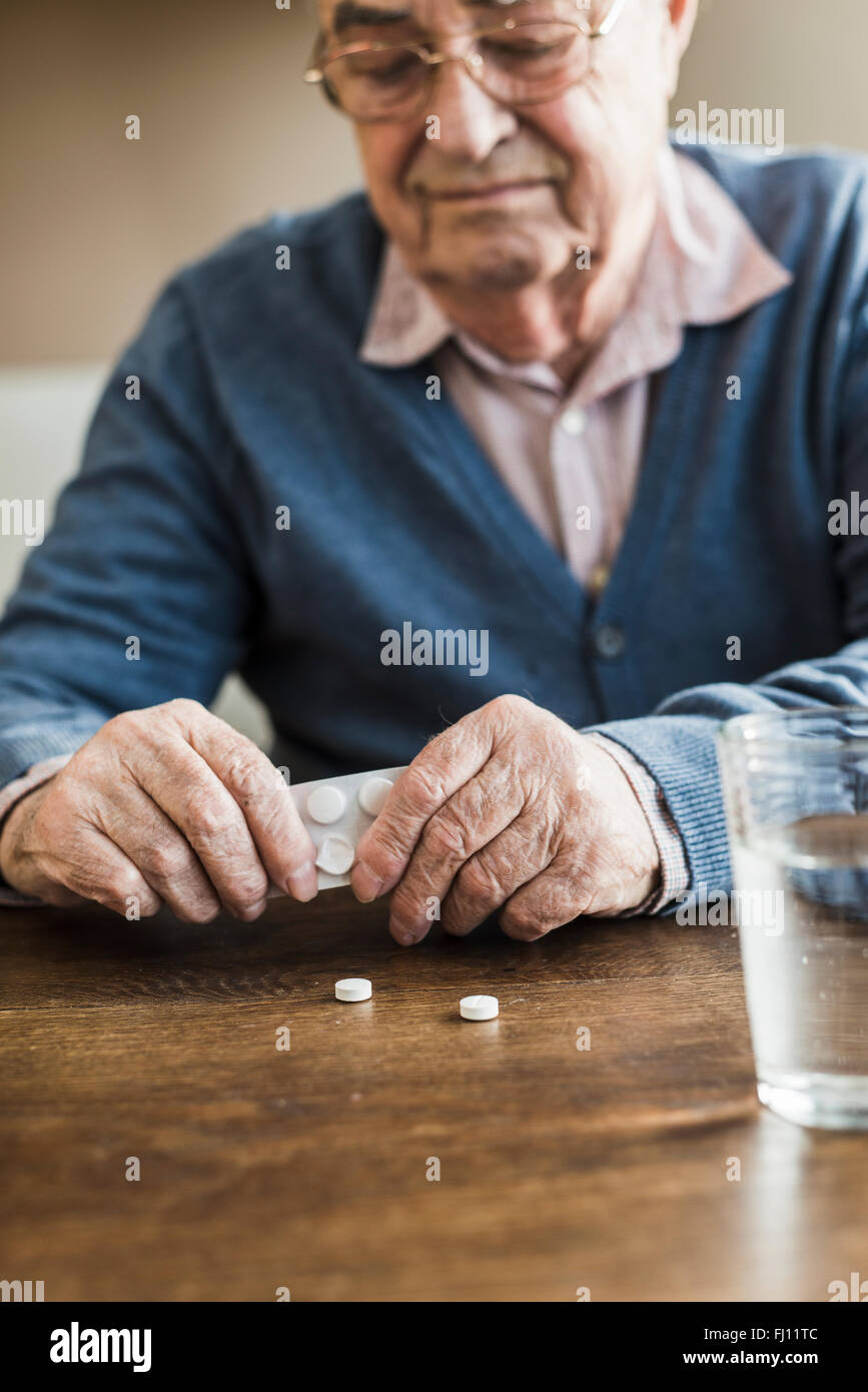 Senior man taking tablets out of blister pack, close-up - Stock Image